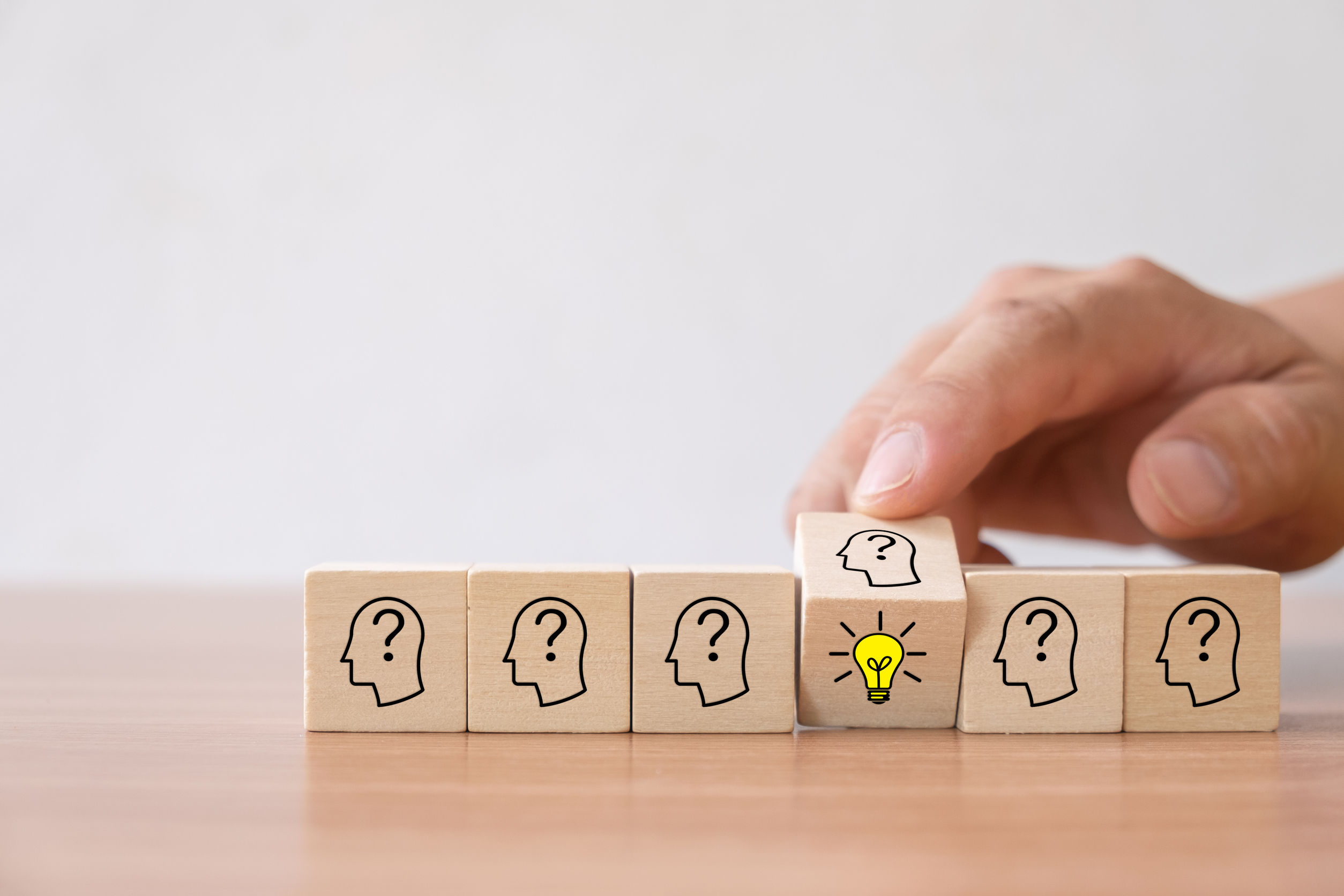 Business concept of creative idea and innovation. Hand flip over wooden cube block with light bulb icon (new idea) and head human symbol have no idea.